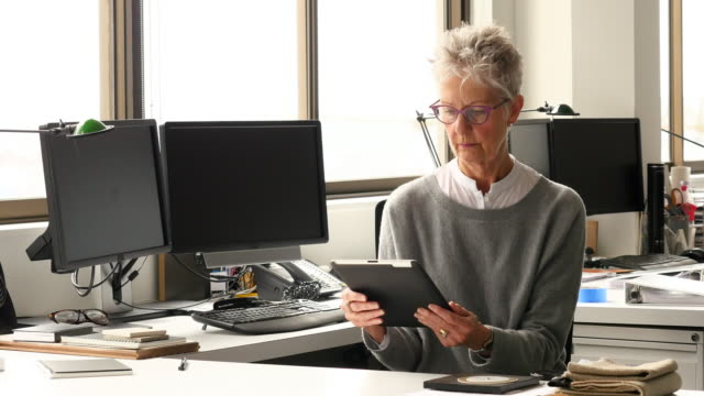 MS Businesswoman working on digital tablet in empty office early in the morning