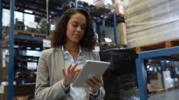 Businesswoman working on digital tablet in warehouse