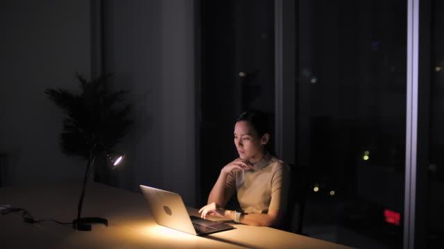 夜のオフィスでラップトップコンピュータで働くビジネスウーマン、勤勉、遅くまで働く - 残業点の映像素材/bロール