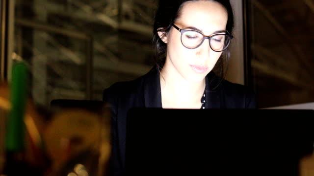 businesswoman working on laptop in dark office - employment issues stock videos & royalty-free footage