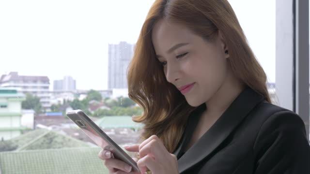 スマート フォンに取り組んでいる実業家。電話を使用して若いアジア女性実業家 - 受ける点の映像素材/bロール