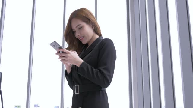 vídeos y material grabado en eventos de stock de empresaria trabajando en un teléfono inteligente. joven empresaria asiática con teléfono - foco difuso