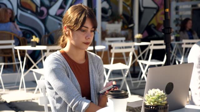 vídeos y material grabado en eventos de stock de ms businesswoman working on smartphone and laptop at outdoor coffee shop - trabajo freelance