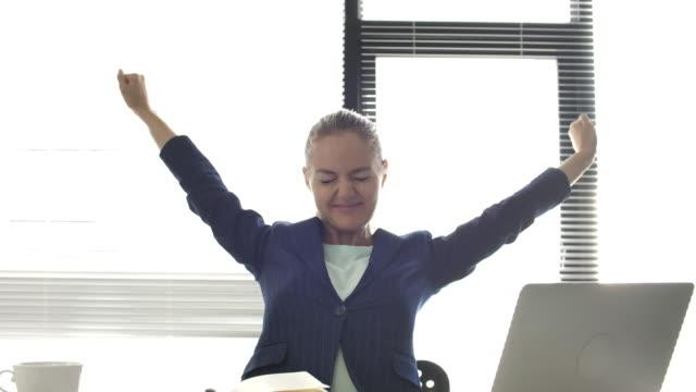 geschäftsfrau arbeitet stretching im büro, feeling happy - kopf nach hinten stock-videos und b-roll-filmmaterial