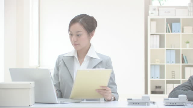 Businesswoman working while businessman dozing off