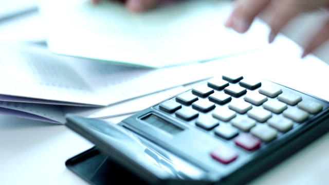 Businesswoman working with calculator in home office