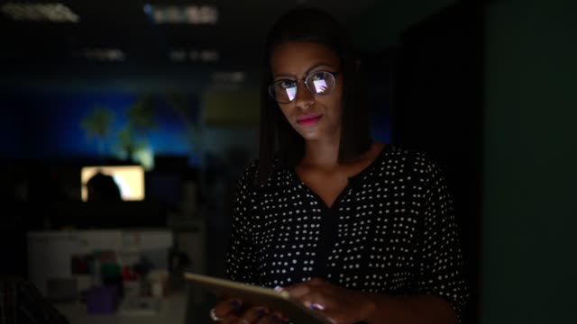 businesswoman working with digital tablet at the office at night - mid adult stock videos & royalty-free footage