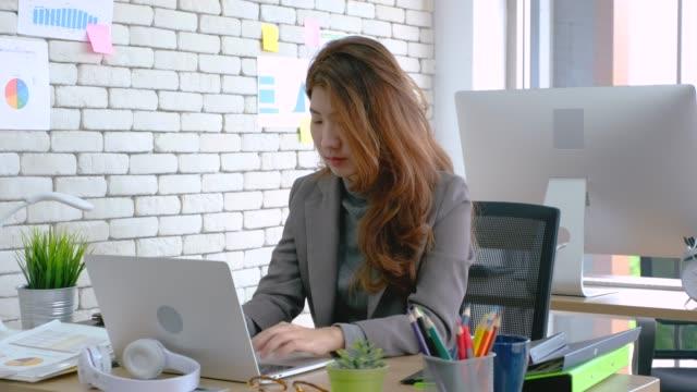 Geschäftsfrau, die mit Laptop am Schreibtisch im modernen Büro arbeitet