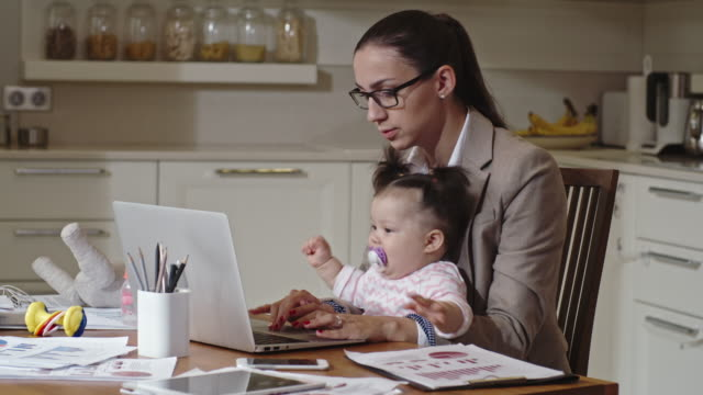 businesswoman working with naughty baby on lap - multitasking stock videos & royalty-free footage