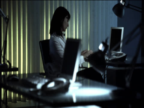 businesswoman works late, sitting at her desk using her computer - only mid adult women stock videos & royalty-free footage