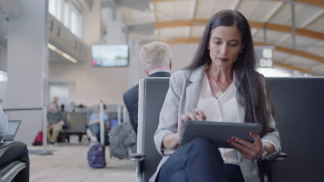 businesswoman works with tablet sitting in airport waiting area near gate. - dipendente video stock e b–roll