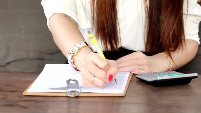 donna d'affari di scrittura relazione e verificare le informazioni - direttrice video stock e b–roll