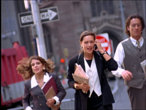 vídeos y material grabado en eventos de stock de 2 businesswomen + businessman running on nyc street / 1 arguing on cellular phone - 1990