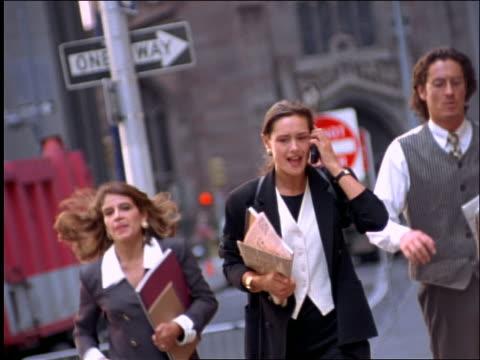 2 businesswomen + businessman running on NYC street / 1 arguing on cellular phone