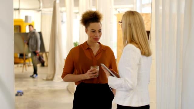 Vrouwelijke ondernemers in creatieve kantoor communiceren