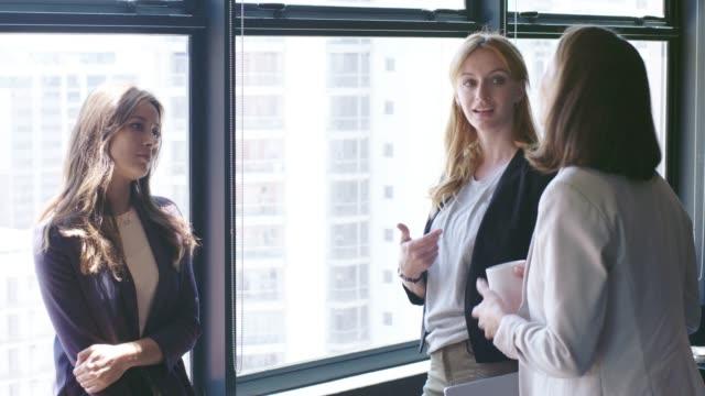 vídeos y material grabado en eventos de stock de hablando por la ventana en la oficina de mujeres empresarias - gesticular