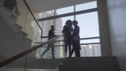 Businesswomen Discussing Documents on Stairs Landing