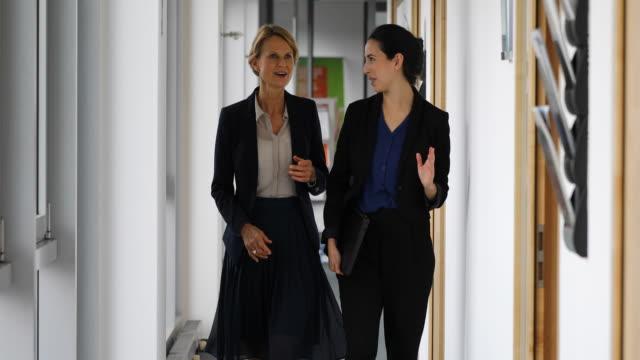 Businesswomen discussing in corridor at office