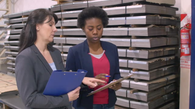 Businesswomen discussing over clipboard in factory