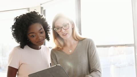 geschäftsfrauen, die diskussion über digital-tablette - überbelichtet stock-videos und b-roll-filmmaterial
