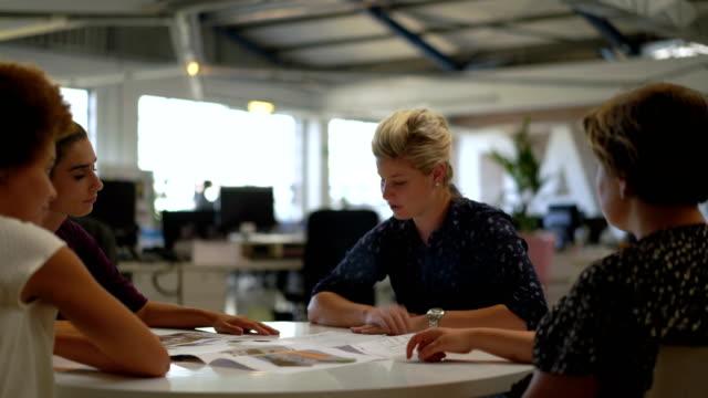 vídeos y material grabado en eventos de stock de businesswomen discussing over documents at desk - compromiso de los empleados