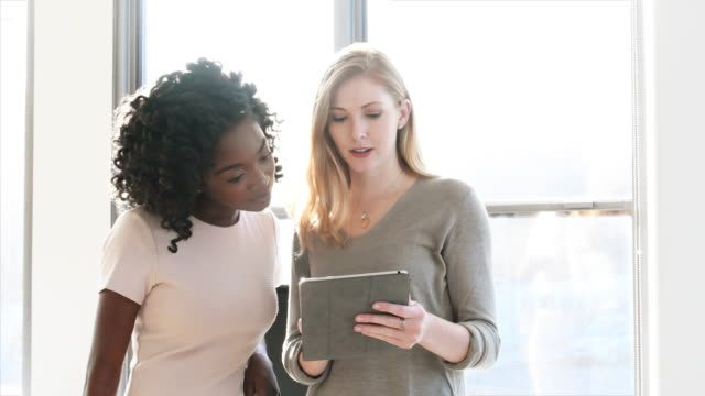Businesswomen discussing over tablet PC