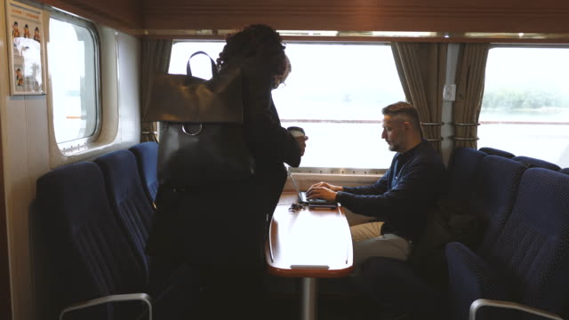 Businesswomen entering while businessman using laptop on passenger craft