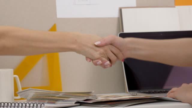 vidéos et rushes de d'accord après discussion femmes d'affaires, se serrant la main - graphisme