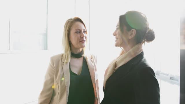 Businesswomen in glass elevator