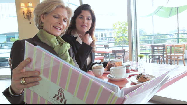 MS Businesswomen sitting in bakery cafe looking at portfolio / Los Angeles, California, United States