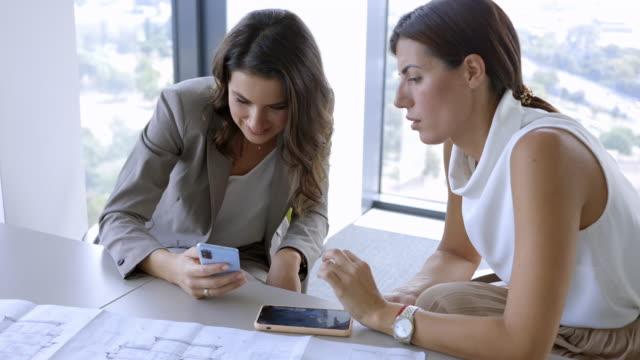vídeos de stock, filmes e b-roll de empresárias sentadas com telefones inteligentes e falando em uma pausa - exposição