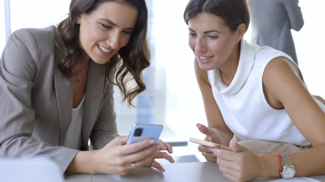 businesswomen sitting with smart phones, scrolling and gossiping cheerfully - curiosity stock videos & royalty-free footage