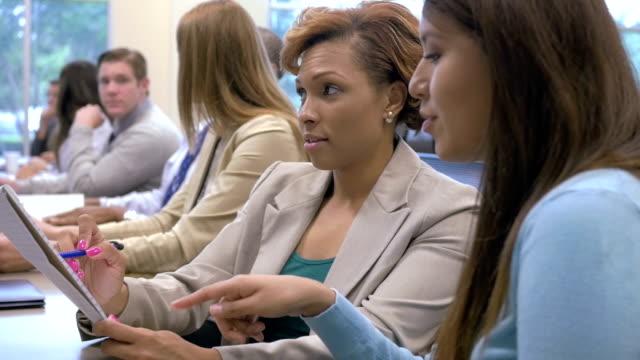 vídeos de stock, filmes e b-roll de businesswomen tomar notas enquanto participa de conferência ou seminário de treinamento prático - feira de emprego
