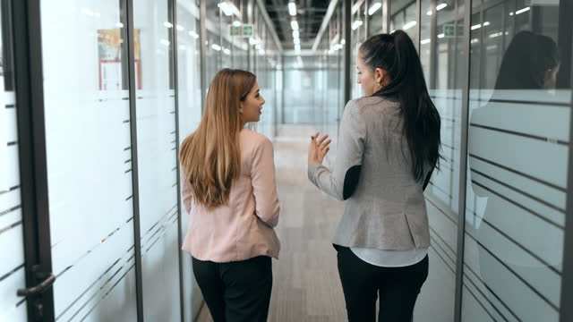 businesswomen talking in office corridors - rear view stock videos & royalty-free footage