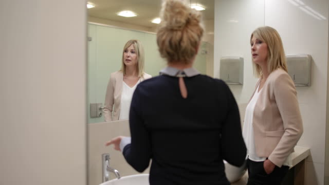businesswomen talking in restroom - gossip stock videos & royalty-free footage