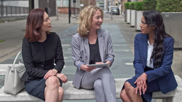 Businesswomen talking on a bench in the streets of London