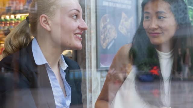 Businesswomen talking, sitting in cafe.