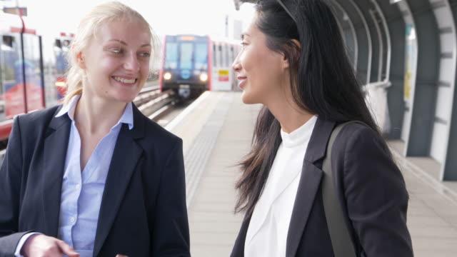 businesswomen talking, waiting for the train. - 駅点の映像素材/bロール