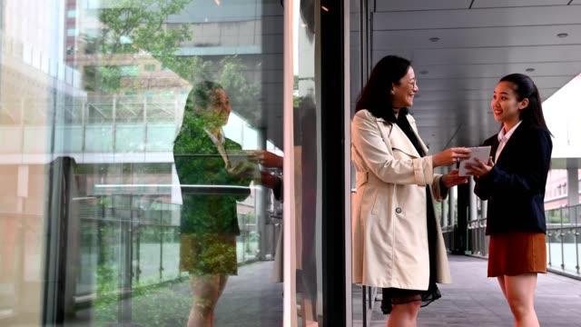 stockvideo's en b-roll-footage met zakenvrouwen praten tijdens het lopen in de gang - driekwartlengte