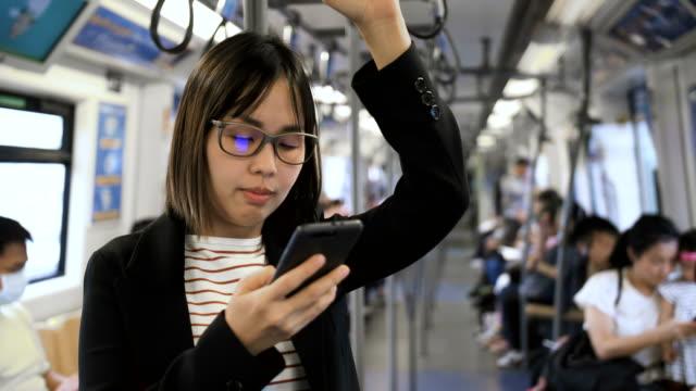 geschäftsfrauen, die nachricht zu schreiben, mit dem skytrain in bangkok. - bahnreisender stock-videos und b-roll-filmmaterial