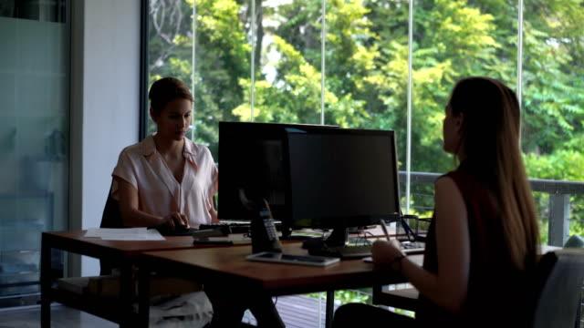 vidéos et rushes de businesswomen using computers at desks in office - téléphone sans fil