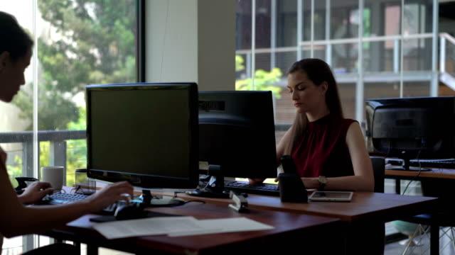 vidéos et rushes de businesswomen using computers by window in office - téléphone sans fil