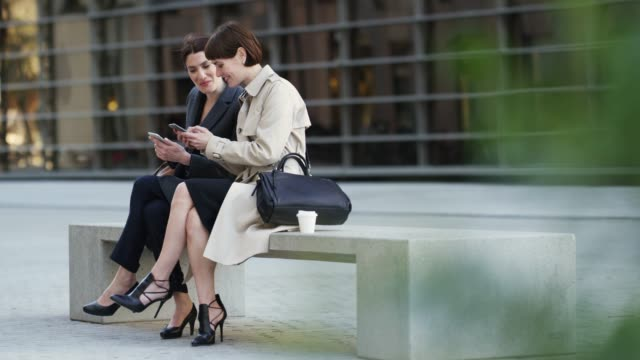 businesswomen using mobile phones on bench in city - two people stock videos & royalty-free footage