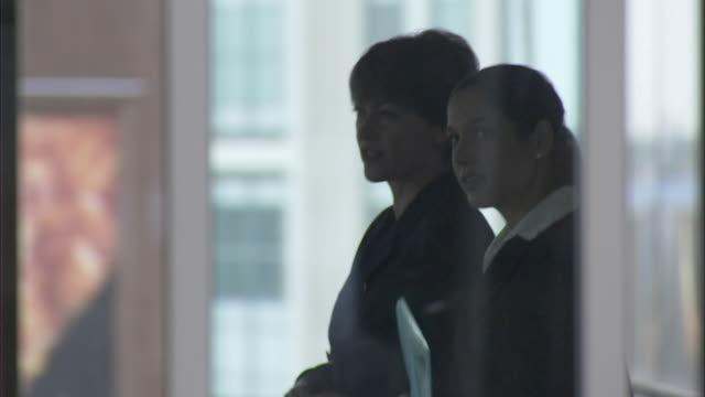 CU DS. Businesswomen walking through office seen from behind window, London, UK