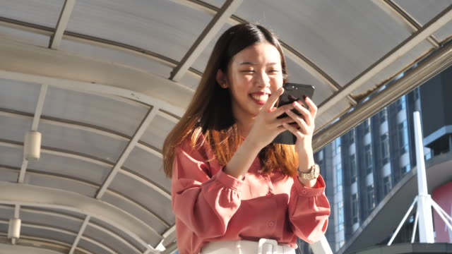 vidéos et rushes de femmes d'affaires marchant avec le téléphone intelligent dans la ville, commuant au concept de travail - professional occupation