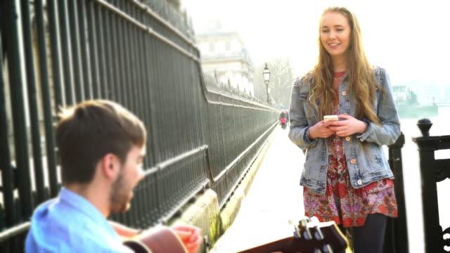 busker e bella giovane donna con telefono. - musicista video stock e b–roll