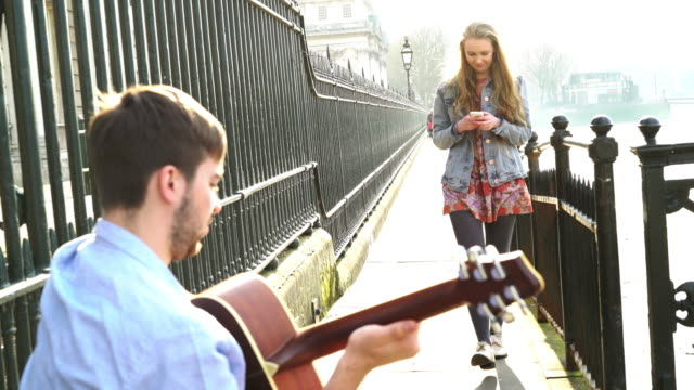 Busker and pretty young woman with phone.