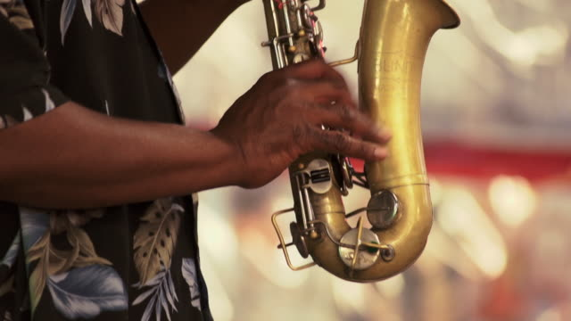 A busker playing a saxophone in time square.  Close up shots of this hands playing the sax.