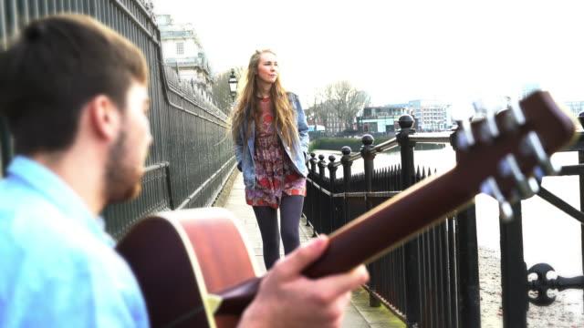 Straßenmusikant spielt Gitarre und hübsche junge Frau.