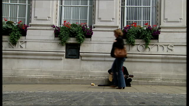 busker playing guitar and singing 'blowin in the wind' and people along past busker sot - plucking an instrument stock videos and b-roll footage